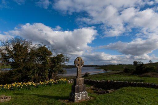 Cruz celta de piedra con lago atrás.