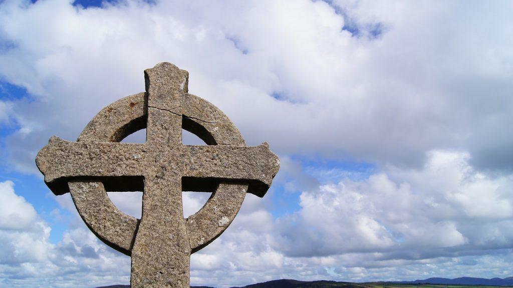 Cruz solar celta de piedra con cielo y montañas de fondo. Donegal, Irlanda.