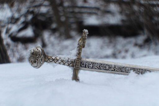 Espada celta en medio del bosque tirada en la nieve.