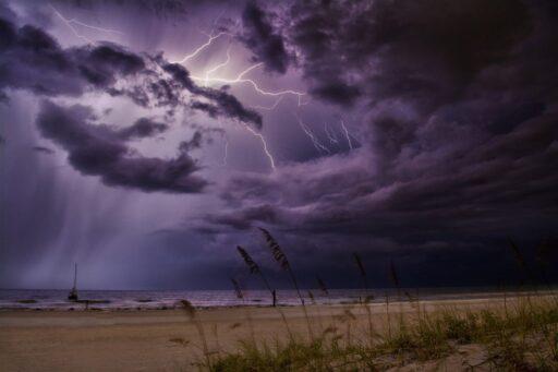 playa con relámpago en el mar en una noche nublada.