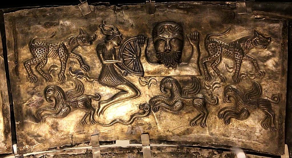 Deidad suprema Taranis grabada en plata, sostiene una rueda en la mano y está rodeado de fieras salvajes.