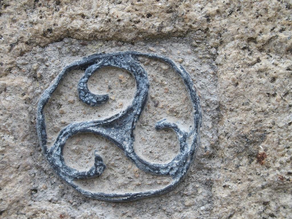 Triskel celta de color azul grabado en piedra.