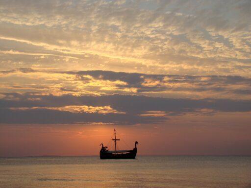Barco vikingo navegando en el atardecer.
