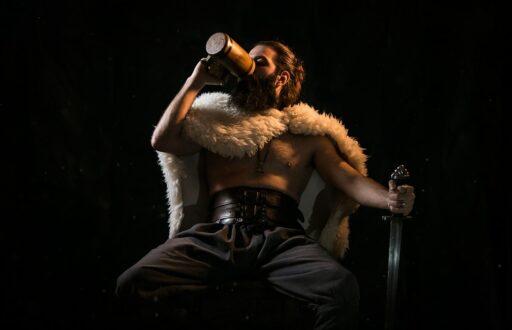 Vikingo sentado con su espada, tomando una bebida.