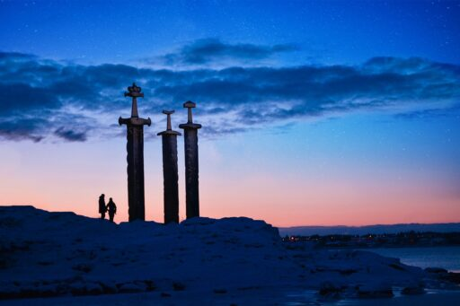 Las tres espadas en la montaña durante el crepúsculo, monumento en Stavanger. Símbolos vikingos y nórdicos.
