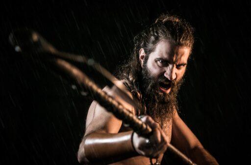 Hombre vikingo atacando con arma.