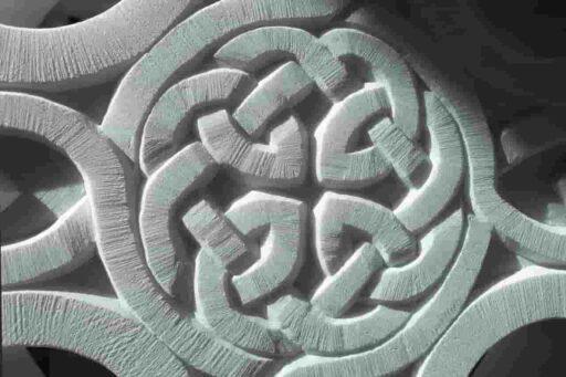 Nudo perenne céltico con guirnalda, grabado en marmol blanco.